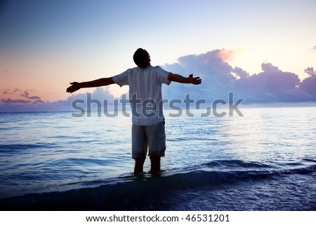 happy young man in sea and sunrise - stock photo