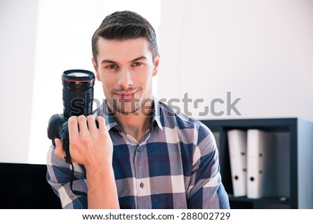 Happy young man in shirt holding photo camera - stock photo