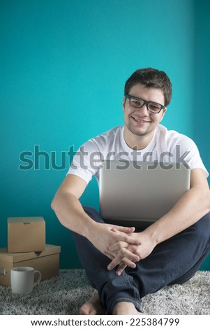 Happy young man in t-shirt sitting at home, working on laptop computer, smiling.  - stock photo