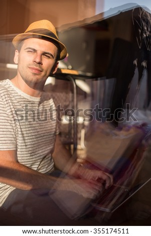 Happy young man in t-shirt sitting on floor at home, working on laptop computer, smiling.