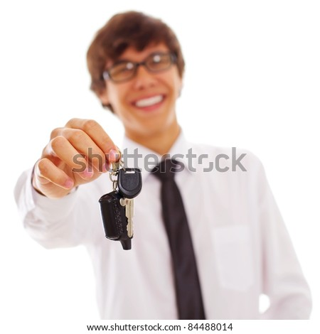 Happy young man in white shirt and black tie holding out car keys isolated on white background, focus on keys