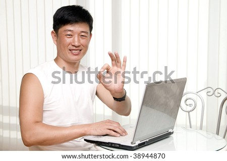 Happy young man indoors, working with laptop, modern interior at background - stock photo