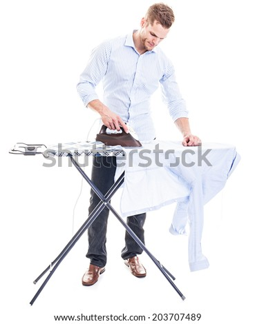Happy young man ironing on a ironing board, isolated on white background - stock photo