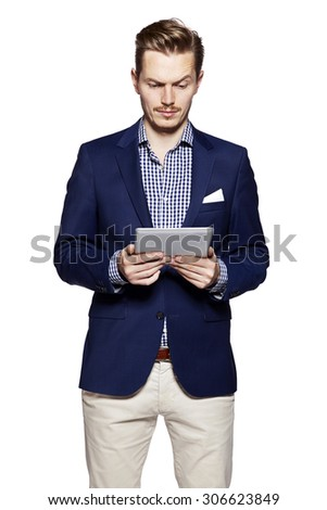 Happy young man is reading from digital tablet. Isolated on white background.  - stock photo