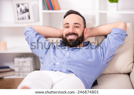 Happy young man is relaxing on sofa and looking at the camera.