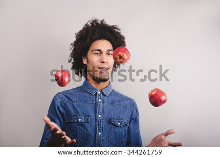 Happy young man juggling with apples on a white background - stock photo