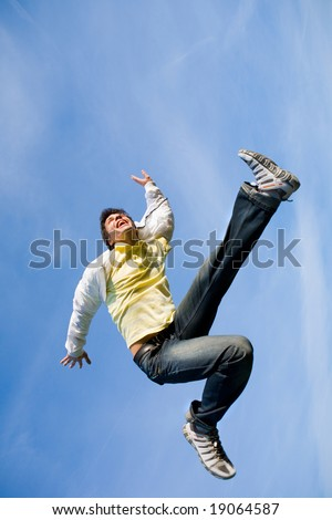 Happy young man - jumping  end flies in blue sky. - stock photo