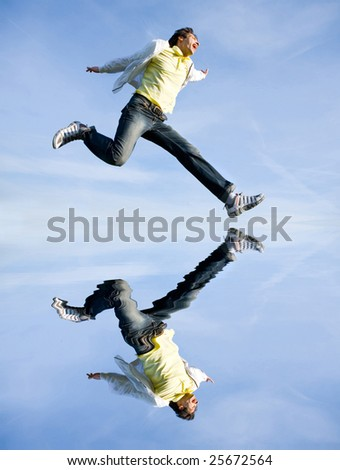 Happy young man - jumping  end flies in blue sky - stock photo