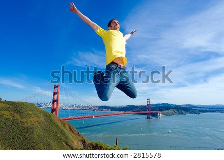 Happy young man jumping high in the air next to the Golden Gate bridge, San Francisco, California - stock photo