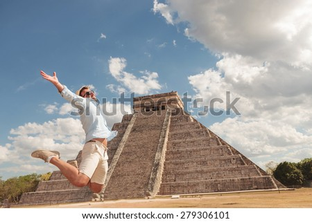 Happy young man jumping of happiness near a pyramid in Chichen Itza, Mexico. - stock photo