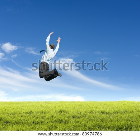 happy young man jumping on meadow against clear sky background
