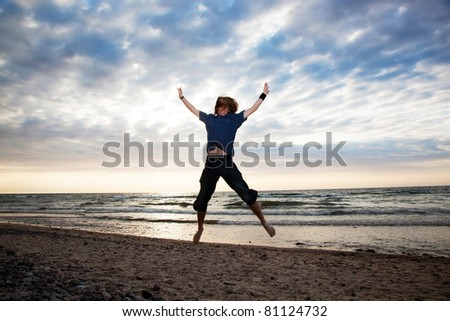 Happy young man jumping on the beach during sunset