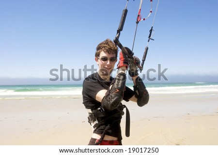Happy young man kiteboarding on the beach