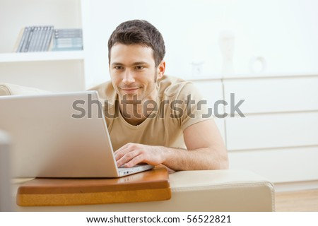 Happy young man laying on sofa at home using laptop computer, smiling. - stock photo