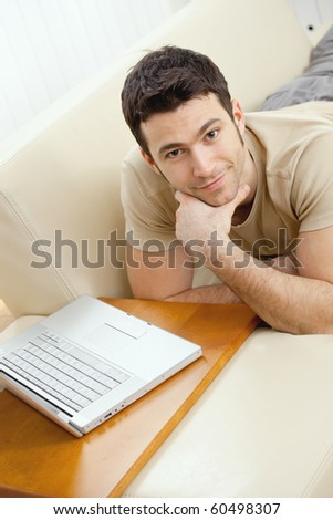 Happy young man laying on sofa at home using laptop computer, smiling. High-angle view. - stock photo