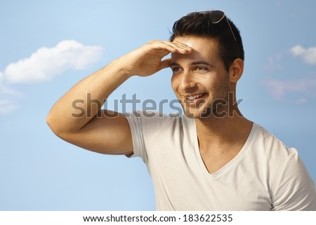 Happy young man looking at distance at summertime over blue sky. - stock photo