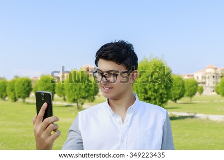 Happy young man looking in phone with great smile. - stock photo