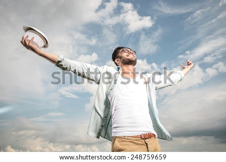 Happy young man looking up to the sky holding both hands in the air, enjoying the sun. - stock photo