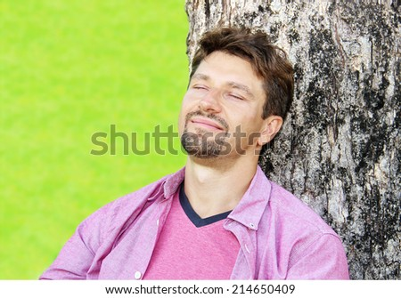 Happy young man lying in grass - stock photo