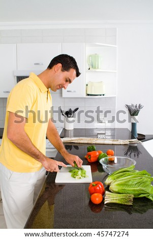 happy young man making a healthy salad in modern kitchen - stock photo