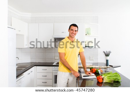 happy young man making a healthy salad in modern kitchen