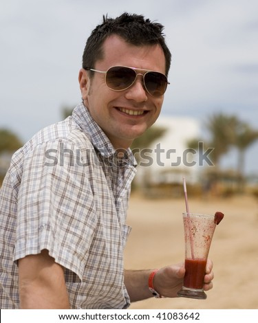 Happy young man on a beach with a glass of strawberry cocktail - stock photo