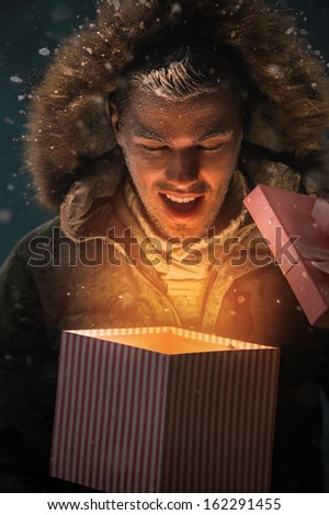 Happy Young Man Opening a Gift Box Outdoors at Night on Christmas Eve - stock photo