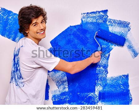 Happy young man paint blue wall at home.