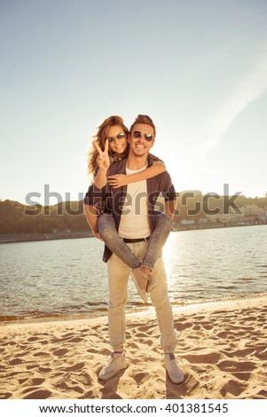 Happy young man piggybacking his girlfriend. - stock photo