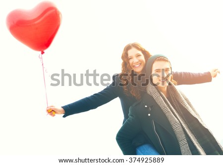 Happy young man piggybacking his girlfriend holding a red heart-shaped balloon  - stock photo