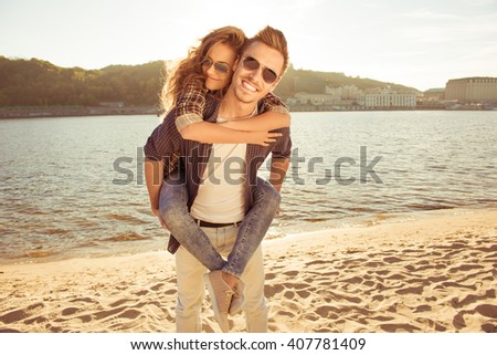 Happy young man piggybacking his pretty woman at the seaside - stock photo