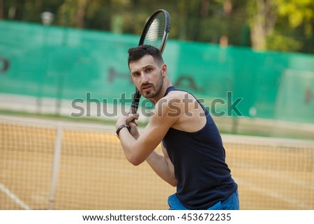 Happy young man playing on tennis court.
