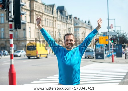 Happy young man posing on the street