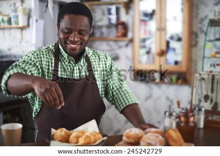 Happy young man powdering buns with vanilla sugar in bakery shop - stock photo