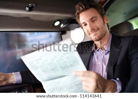 Happy young man reading newspaper in luxury car, smiling. - stock photo
