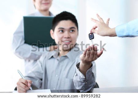 Happy young man receiving a car key after signing a document.Focus on the key. - stock photo