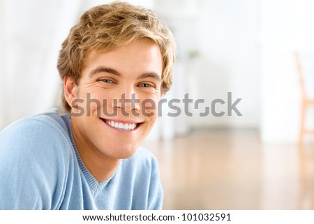 Happy young man relaxing at home looking at camera smiling