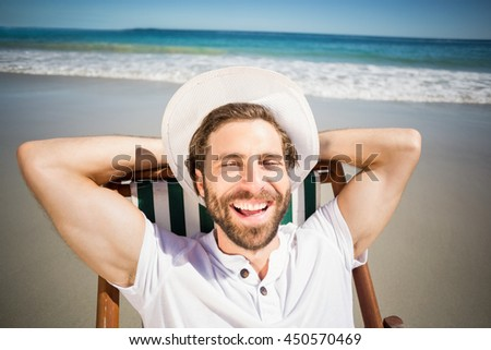 Happy young man relaxing on armchair at beach - stock photo