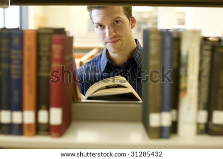 Happy young man researching info at a library - stock photo