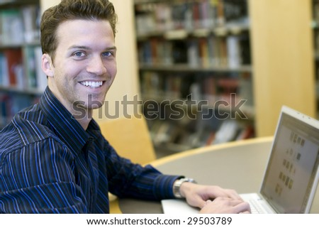 Happy young man researching information - stock photo