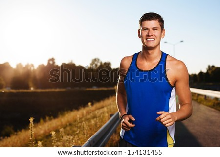 Happy young man running during sunset - stock photo