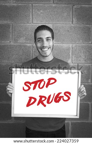 happy young man showing and displaying board with text: Stop Drugs Campaign