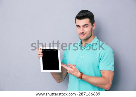 Happy young man showing blank tablet computer screen over gray background. Looking at camera - stock photo