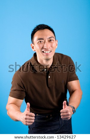 Happy young man showing thumbs up sign that everything is great. - stock photo