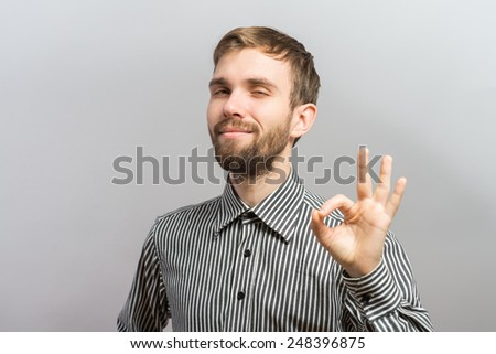 happy young man shows OK - stock photo