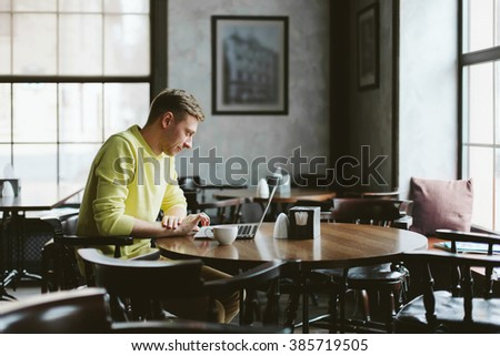 Happy young man sits at a table in an empty cafe with a cup of coffee and working on laptop - stock photo