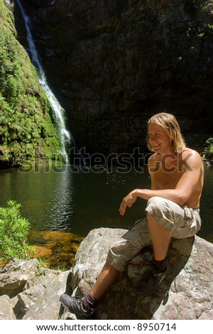 Happy young man sits next to waterfall in awesome mountains. Shot in the Kromrivier - Du Toitskloof Nature Reserve, near Paarl, Western Cape, South Africa.