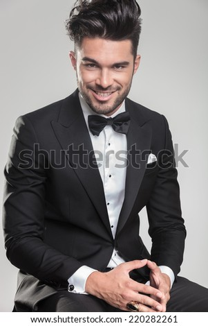 Happy young man sitting and holding his hands together while smiling for the camera. - stock photo