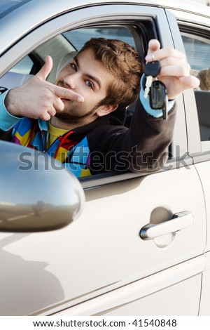 Happy young man sitting in a new car holding out keys - stock photo