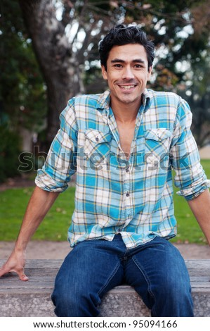 Happy young man sitting in a park - stock photo